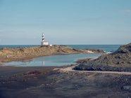 Rocky coast and beacon tower — Stock Photo