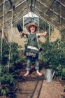 Boy fooling around in greenhouse — Stock Photo
