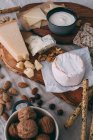 Cheese board with nuts and crostini — Stock Photo