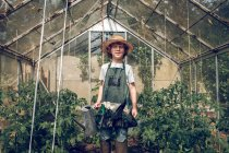 Boy standing with watering can in greenhouse — Stock Photo