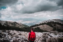 Backpacker standing in mountains — Stock Photo