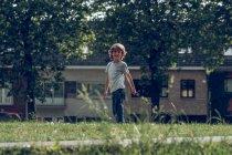 Улыбающийся мальчик позирует на лужайке — стоковое фото