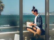 Joven mujer leyendo libro en balcón por la orilla del mar . - foto de stock