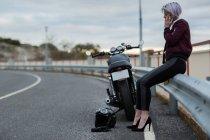 Woman talking on smartphone next to motorbike — Stockfoto