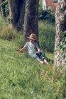 Little boy in hat sitting under tree — Stock Photo