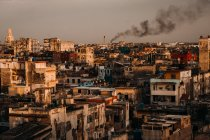 Old shabby city buildings and houses with black smoke on background at sunset, Cuba — Stock Photo