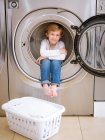 Cute preschooler boy sitting inside washing machine and looking in camera. — Stock Photo
