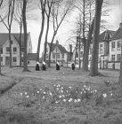 Preto e branco tiro de freiras em vestidos pretos andando no prado no parque da cidade com arquitetura antiga, Bélgica . — Fotografia de Stock