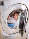 Niño de edad elemental con linterna en el interior de la lavadora con libro . - foto de stock