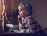 Petit garçon assis avec livre à table — Photo de stock