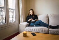 Woman relaxing with book at home — Stock Photo