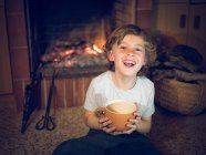 Laughing boy sitting at fireplace with cup — Stock Photo