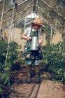 Kid watering plants in greenhouse — Stock Photo