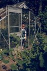 Boy standing in font of greenhouse — Stock Photo