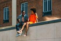 Afro-américain et femme riant tout en étant assis sur la frontière sur la rue de la ville — Photo de stock