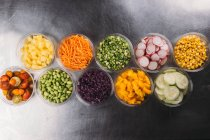 Set of plastic bowls of assorted vegetarian ingredients for food preparation — Stock Photo