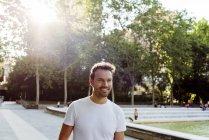 Красивий хлопець у біла Маєчка посміхається і прогулянки у парку на сонячний день — стокове фото