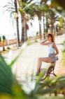 Femme en vêtements d'été assis sur un banc dans un parc tropical — Photo de stock