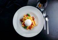 Fettuccine di pasta con carne, abitazione e capra sfera di formaggio sulla zolla bianca — Foto stock