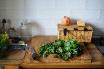 Grüne Spinatblätter auf einem Holzhackbrett in der Küche — Stockfoto