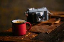 Esmalte cafezinho na superfície de madeira rústica com câmera retro — Fotografia de Stock