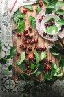 Lay plat de cerises, dénoyauteur de cerise et vert laisse sur la table rustique — Photo de stock