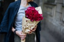 Крупным планом женщины, держащей букет розовых пионов в оберточной бумаге — стоковое фото