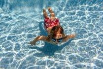 Preschooler swimming underwater in blue pool, overhead view — Stock Photo