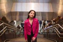 Портрет симпатичной брюнетки в розовой куртке, стоящей на ступеньках подполья и смотрящей в камеру — стоковое фото