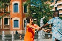 Uomo afroamericano e donna che sorride e ballano insieme su priorità bassa della Fontana a street vaga — Foto stock
