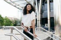 Rindo afro-americana em pé perto de corrimão de escadaria na rua da cidade — Fotografia de Stock
