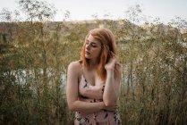 Руда молоду жінку в декоративних сукні, торкаючись волосся і постановки в природі — стокове фото