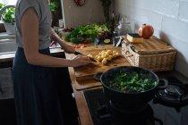 Femme coupant des pommes de terre sur planche à découper en bois et feuilles d'épinards en pot sur cuisinière à gaz — Photo de stock