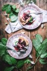 Top view of plates with cherry pie slices served with ice cream on table among green leaves — Stock Photo