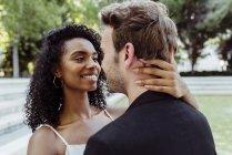 Jolie femme souriante regardant l'homme tout en permanent dans le parc et en touchant son cou — Photo de stock