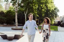 Lächelndes multiethnisches Paar läuft Händchenhaltend im Stadtpark — Stockfoto