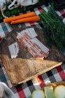 Плед с Советом и служил беконом среди свежие овощи очищенные для приготовления пикник — стоковое фото