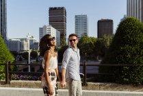 Glückliches multiethnisches Paar lächelnd und Händchenhaltend, während es an einem sonnigen Tag gemeinsam auf der Straße der Stadt spaziert — Stockfoto