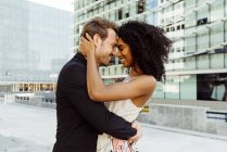 Elegant multiracial couple embracing in modern city — Stock Photo
