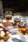 Menschliche Hand halten Glas Weißwein auf Holztisch im freien — Stockfoto