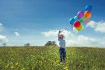 Счастливый ребенок, стоя с красочными шарами на поле с цветут желтый полевые цветы и глядя вверх — стоковое фото