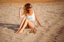 Chilling woman in summer clothes sitting on sandy beach — Stock Photo