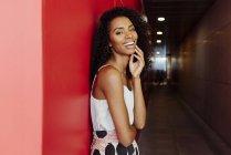 Улыбающаяся афроамериканка в элегантном наряде, стоящая на красном фоне — стоковое фото