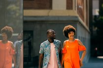 Stylish African American man and woman laughing and walking on city street together — Stock Photo