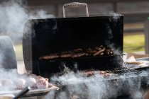 Raw burger patties roasting on grid of barbecue grill outdoors — Stock Photo