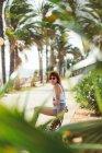 Femme mince en maillot de bain et short en denim assis sur un banc dans un parc tropical et regardant la caméra — Photo de stock