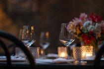 Primer plano de la mesa de ajuste decorada con velas y flores por la noche - foto de stock