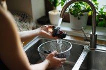 Людські руки, миття виноград під раковиною торкніться кухні — стокове фото