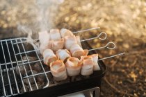 Close-up of portable griddle with burning charcoal and skewers with bacon strips grilling — Stock Photo