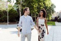 Lächelndes Paar Händchen haltend beim Spaziergang im Stadtpark — Stockfoto